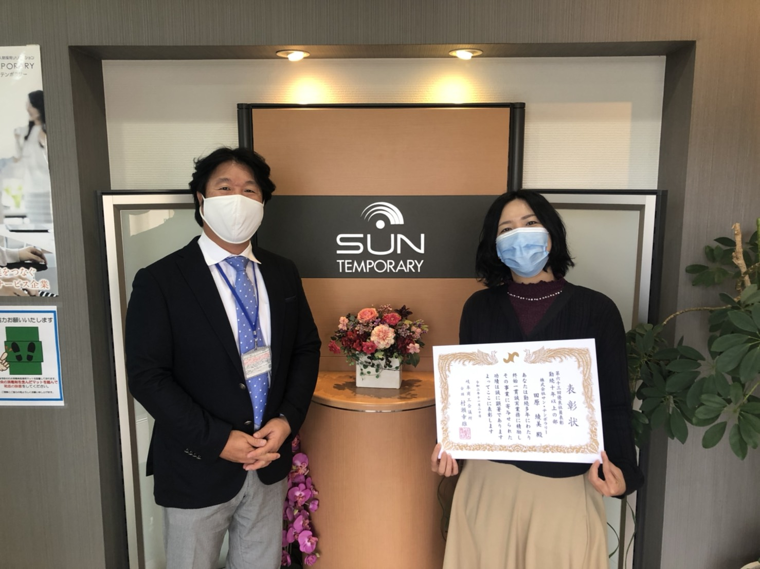 会社玄関で撮影した田原さんと代表後藤の写真。